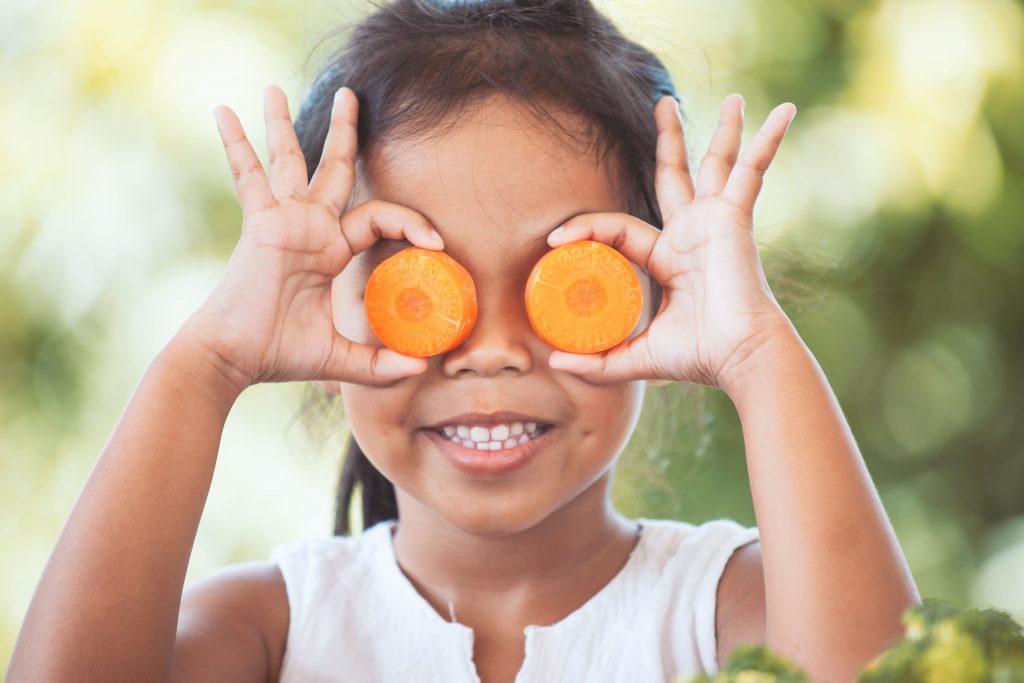 small girl holding carrot slices over eyes