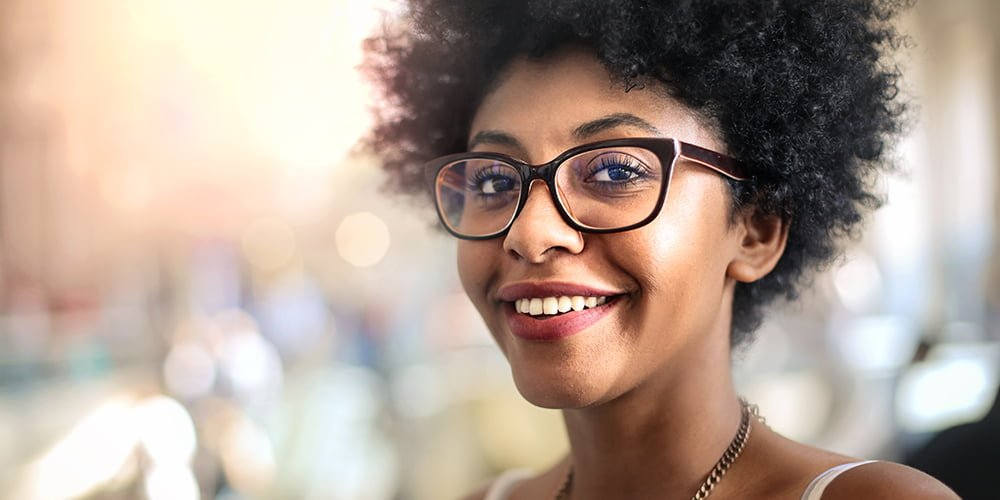 woman wearing dark rimmed glasses with Bokeh background