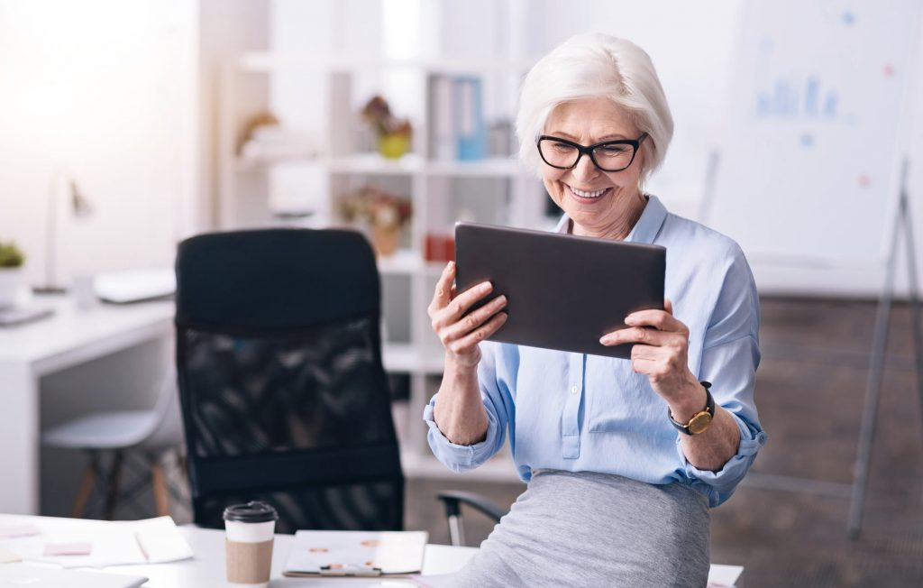 older woman wearing glasses looking at a tablet in office