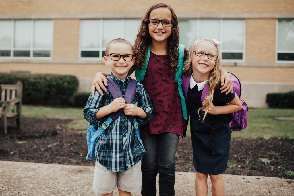 3 kids wearing glasses in front of school