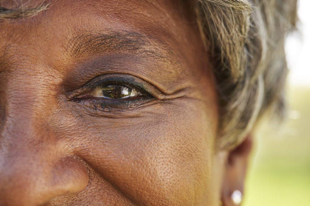 Close Up Of Smiling Senior Woman's Eyes In Park