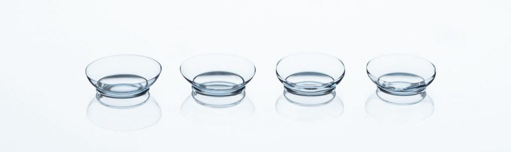 close up view of contact lenses arranged on white backdrop