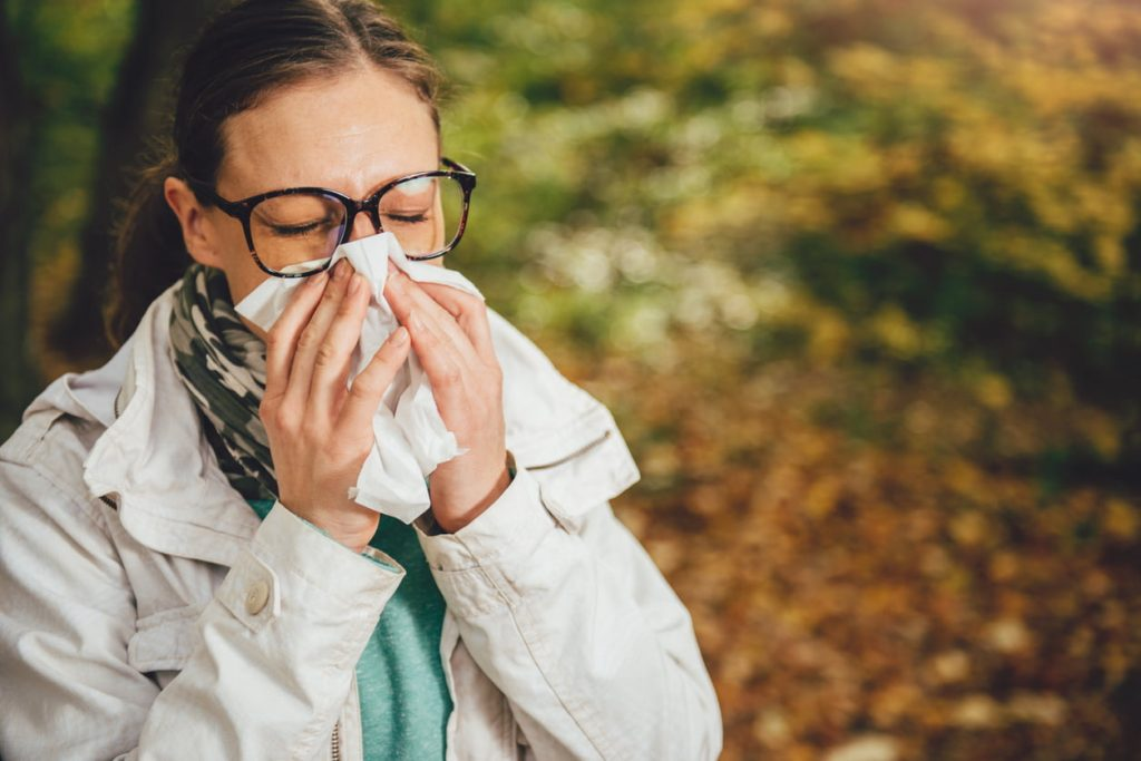 Woman with seasonal allergies blowing her nose in the park
