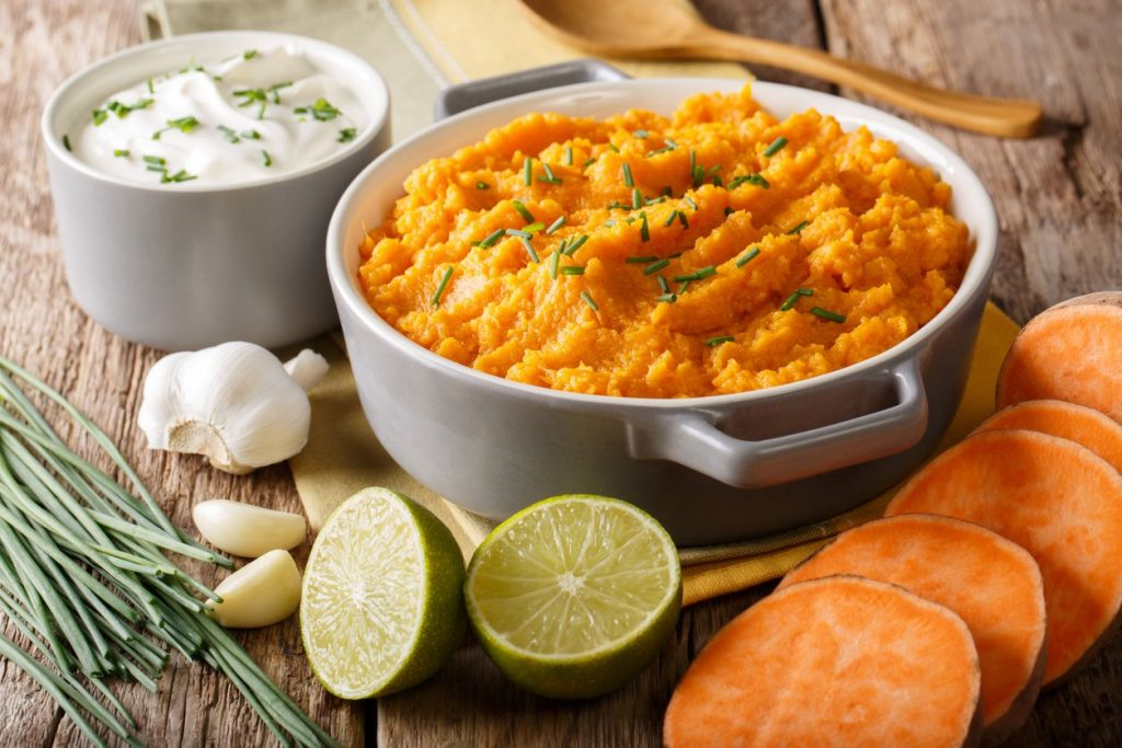 Freshly prepared mashed sweet potatoes with herbs, garlic and lime close up in a pot. horizontal