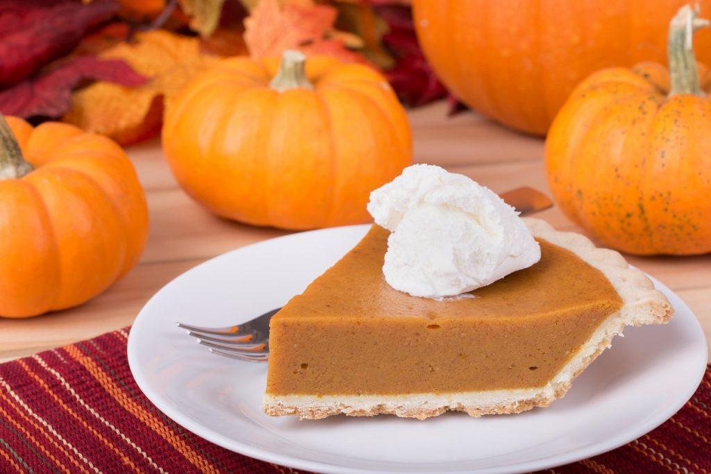 pumpkin pie slice with pumpkins in the background