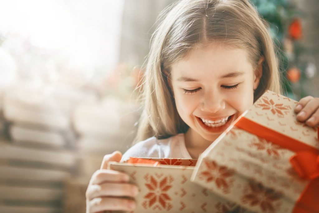Happy holidays! Cute little child opening gift at Christmas.
