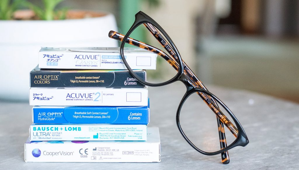 a stack of contact lens boxes with glasses perched next to them