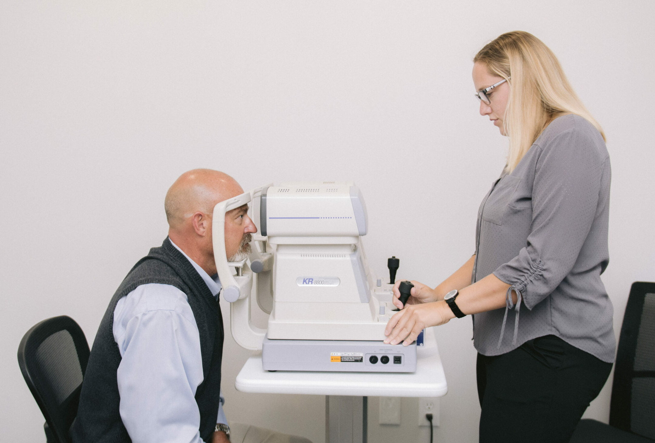 patient sitting in front of an air puff tonometer during an eye exam